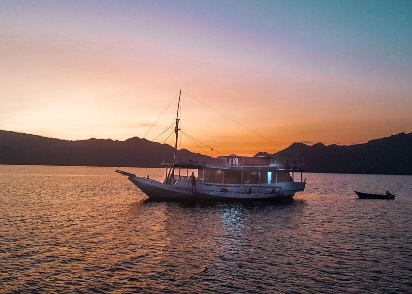 Boot im Sonnenuntergang auf dem Wasser im Komodo Nationalpark während einer mehrtägigen Bootstour