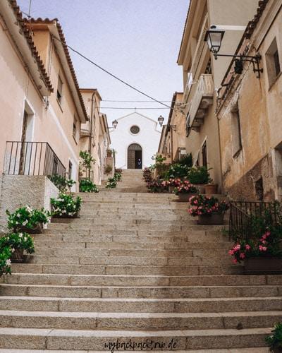 Italienische Altstadt mit Gebäuden links und rechts und einer Treppe in der Mitte die zu einer Kirche führt.