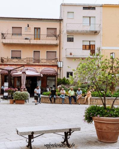 Italienischer Dorfplatz mit einigen Bewohner und alten Gebäuden.