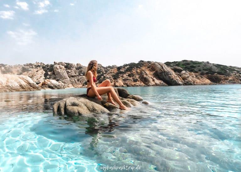 Frau sitzt auf Fels im Wasser