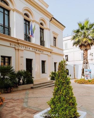 Bibliothek im historischen Baustiel umgeben von grünen Palmen
