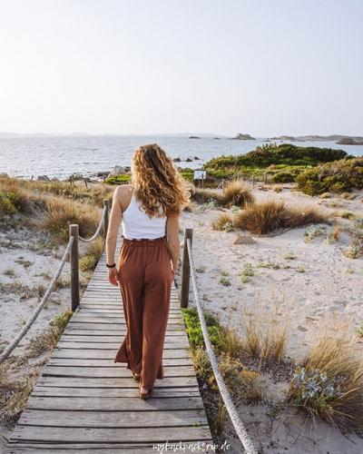 Frau läuft auf Steg durch Dünen am Meer