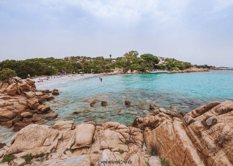Bucht mti Felsen und Sandstrand und türkisenem Wasser